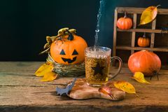 Halloweenowy wakacyjny pojęcie z filiżanką herbaciana i dyniowa dekoracja na drewnianym stole fotografia royalty free