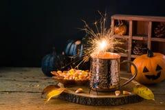Halloweenowy wakacyjny pojęcie z filiżanką, sparklers, cukierek kukurudzą i bani dekoracją na drewnianym stole, fotografia stock