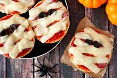 Halloweenowych mamuś mini pizz zasięrzutna scena na nieociosanym drewnie Obrazy Royalty Free