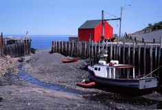 Halls Harbour Nova Scotia at Low Tide. Fishing boat and skiffs grounded on the sand at low tide in Halls Harbor, Nova Scotia. Located on the Bay of Fundy, the Stock Image