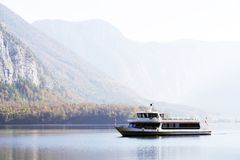 HALLSTATT, AUSTRIA, 19 OCTOBER, 2018: Tourist ship on the famous Hallstatt lake in a autumn foggy morning stock images