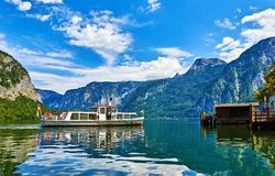Hallstatt Austria walking travelling boat arriving. Hallstatt, Austria. Touristic pleasure boat arriving to the old wooden dock at lake Hallstattersee among Stock Image