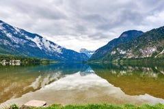 Hallstatt jezioro przy deszczowym dniem z kaczkami, chmurami i odbiciami niebo w wodzie, Salzkammergut region, Austria zdjęcie stock