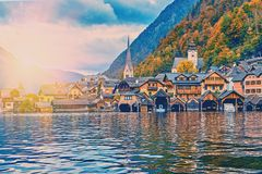 Hallstatt mountain resort village with famous church, traditional alps houses and wooden rural boat houses at Hallstatt lake royalty free stock images