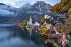 Hallstatt mountain village in twilight in fall, Salzkammergut, Austria. Scenic picture-postcard view of famous historic Hallstatt mountain village with Royalty Free Stock Photos