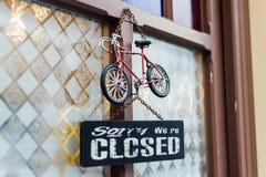 HALLSTATT, OOSTENRIJK - DECEMBER 2018: deuruithangbord Droevig zeggen zijn wij gesloten met stuk speelgoed hierboven fiets stock fotografie
