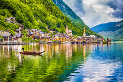 Hallstatt with traditional Plätte boat, Salzkammergut, Austria. Scenic picture-postcard view of famous Hallstatt mountain village with Hallstätter See and royalty free stock image