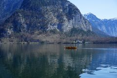 Small scenic village with snowy mountain on the background. Hallstatt waterfront with a great view of snowy mountain on the back Royalty Free Stock Image