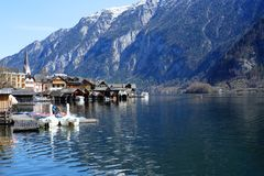 Small scenic village with snowy mountain on the background. Hallstatt waterfront with a great view of snowy mountain on the back Royalty Free Stock Images