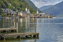 Hallstatt wioski krajobraz z starymi budynkami odbijał w błękitnym jeziorze z drewnianymi pokładami w przedpolu zdjęcie royalty free