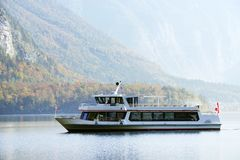 HALLSTATT, AUSTRIA, 19 OCTOBER, 2018: Boat on the famous Hallstatt lake in a autumn foggy morning royalty free stock images