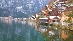 The lakeside housing of Hallstatt, Salzkammergut, Austria. Hallstatter see lake with old housing of Hallstatt, its lakeside promenade, port with wooden garages stock footage