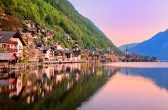 Halltatt stad som reflekterar i sjön på solnedgången, Salzkammergut, A Arkivfoto