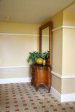 Hallway. Decor, buffet with vases, plant and mirror in corner Royalty Free Stock Photography