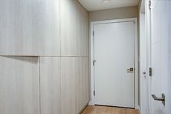 Hallway features ivory cabinets and taupe walls. Fitted with white doors stock images