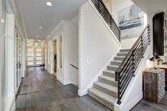 Hallway features a staircase with gray carpet runner. Hallway features a staircase lined with gray carpet runner and metal horizontal hand rails. Long hallway Royalty Free Stock Photos
