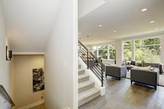 Hallway features white ceiling dotted with pot lighting. Over modern style family room and a staircase with horizontal hand rails. Northwest, USA Stock Image