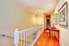 Hallway with hardwood floor and white railing to staircase. Royalty Free Stock Images