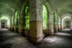 Hallway in a hospital. Abandoned mental hospital in Italy with a beautiful hallway where the light poors through the overgrown windows giving a green effect stock photography