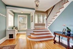 Hallway interior in blue tones, columns and hardwood floor. View of stairs. Stock Image