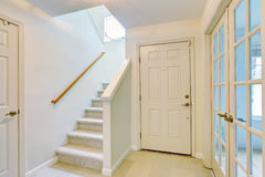 Hallway interior in light tones with hardwood floor and carpet stairs Royalty Free Stock Photos