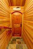 Hallway interior with pannel wooden trim. Door to home wine cellar. Stock Image