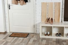 Hallway interior with shoe rack and mat. Near door royalty free stock image