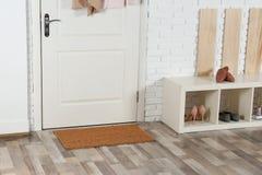 Hallway interior with shoe rack and mat. Near door royalty free stock photo