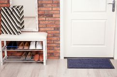 Hallway interior with shoe rack, mirror and mat. Near door stock images