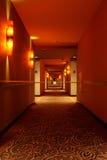 Hallway at Night. Deserted hallway perspective, illuminated at night with soft reddish light setting mood and tone royalty free stock photo