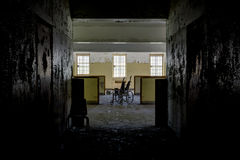 Hallway Opening to Cubicles & Lone Wheelchair - Abandoned Hospital royalty free stock photography