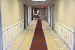 Hallway painting. Renovating and repainting office building hallway walls using spray method and taping to provide protection of carpet stock photography