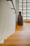 Hallway with starcase and long vase by the glass brick window Royalty Free Stock Photos
