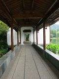Hallway in Traditional Chinese Garden. A long wooden hallway in a traditional Chinese garden stock image