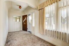 Hallway with view of opened front door and carpet floor Stock Images
