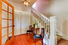 Hallway with white staircase and hardwood floor. Stock Photo
