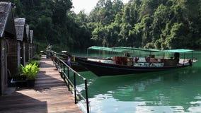 Halmtäcka-tak hus vid sjön fartyget som binds till pir, guppar på vågorna, sjöCheow LAN khaonationalparksok thailand arkivfilmer