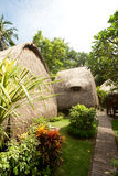 Halmtäcka takbungalowen på den tropiska semesterorten Royaltyfria Bilder