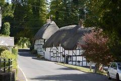 Halmtäckte stugor på Wherwell hampshire england Arkivbilder