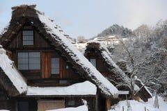Halmtäckte takhus som täckas i insnöad vinter Arkivfoto