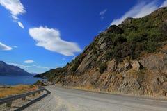 Halna droga obok jeziora z niebieskim niebem Obraz Royalty Free