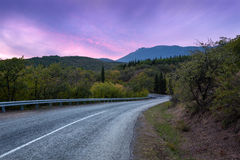 Halna droga przez lasu przy kolorowym zmierzchem Podróż z powrotem Fotografia Royalty Free
