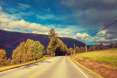 Halna droga przy zmierzchem z chmurnym niebem Fotografia Stock