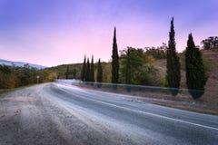 Halna droga z zamazanymi samochodami w ruchu przy zmierzchem Obrazy Royalty Free