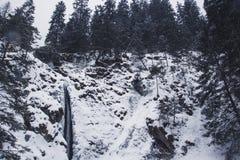 Halna siklawa z skałami i falezami zakrywającymi z śnieżnym durin fotografia stock