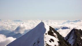 Halnego arywisty stojaki na szczyt grani z wielkim widokiem behind zdjęcie stock