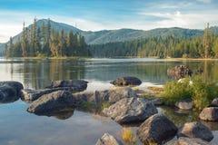 Halny jezioro z dużymi skałami na przedpolu Obraz Stock
