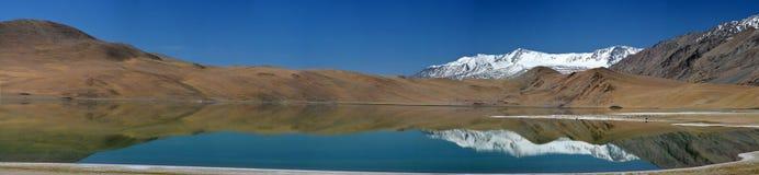 Halny jezioro z jaskrawą turkus wodą fotografii pa i lustrzaną powierzchnią, w którym odbijają góry z śnieżystym szczytem Obraz Stock