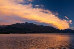 Halny jezioro, zmierzch, Dramatyczne pomarańcz chmury Zdjęcia Stock