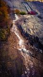 Halny kołysanie się nad światłem słonecznym i chmury spadamy kaskadą góra wodnego spadek Obrazy Stock